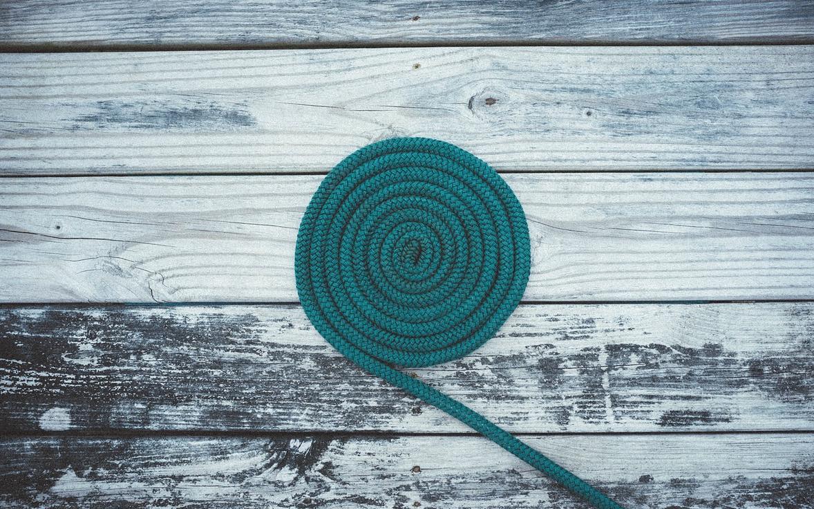 türkisfarbenes Seil zu Spirale gerollt auf verwittertem Holzuntergrund.